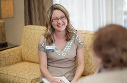 staff member sitting on a couch smiling at a resident in a wheelchair