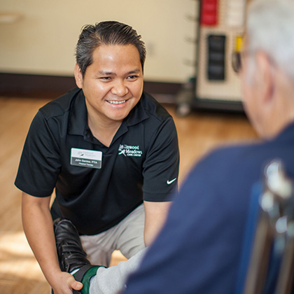 staff member assisting resident in the rehab room