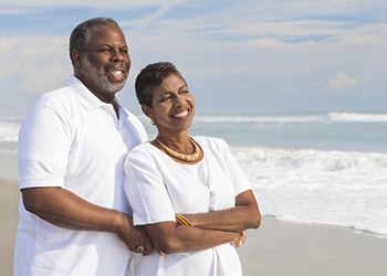 couple dressed in all white smiling and looking at the ocean