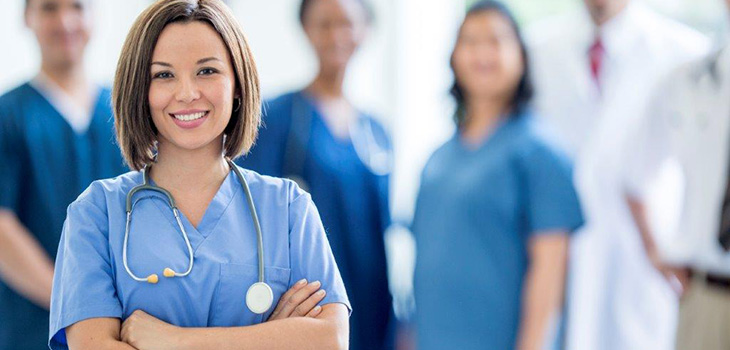 nurse with stethoscope with more staff in the background