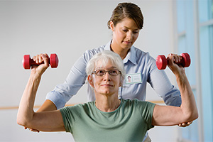 female resident lifting hand weights with a therapist