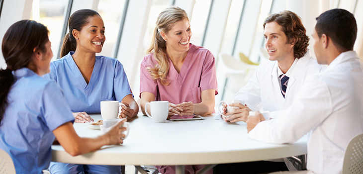 nurses and doctors seated at a round table drinking coffee