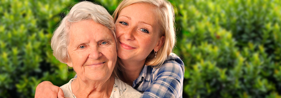 smiling young woman with her arms around her grandma