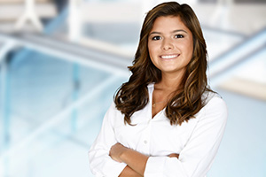 smiling young female professional with her arms crossed
