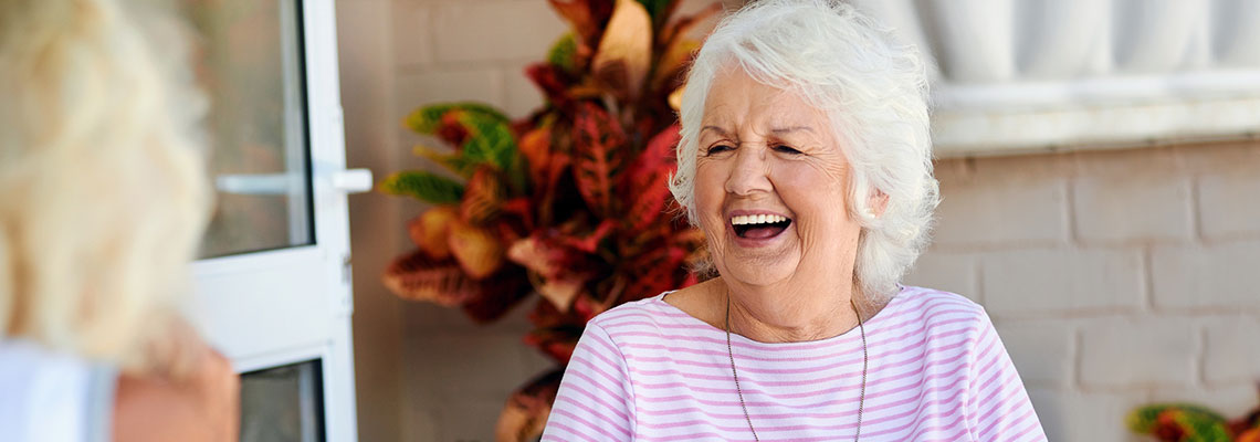 laughing woman seated outside on a patio with a colorful plant in the background