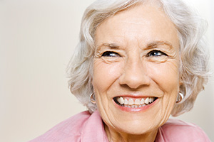 elderly woman smiling and looking off to the side