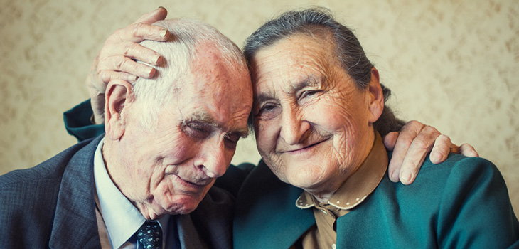 sweet elderly couple sitting with their heads tilted together