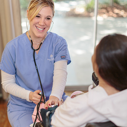 Nurse smiling while taking residents blood pressure