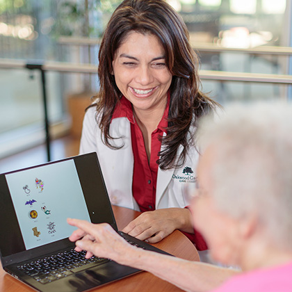 Nurse with resident viewing images on laptop