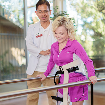 Rehab resident with rehab staff member on parallel bars