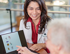 Nurse smiling with resident working on laptop