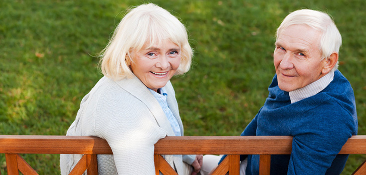 A couple sitting on a bench together holding hands