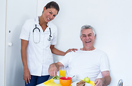 A nurse serving a resident food in bed