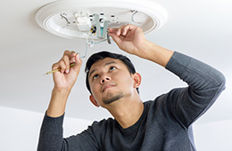 A man fixing an electrical fixture on the wall