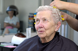 Woman having her hair put up in curlers