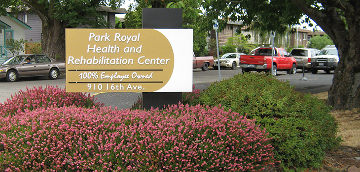 Park Royal Health and Rehabilitation Center sign out front with bushes filled with flowers below