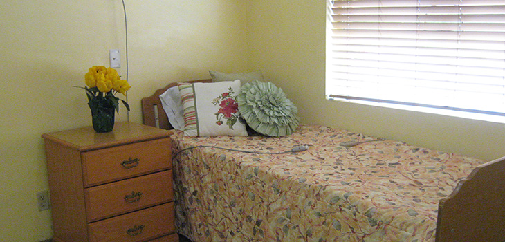Resident room with nicely made bed and tulips by the bedside