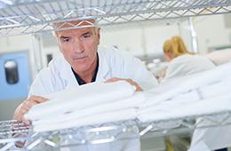 A staff member folding laundry