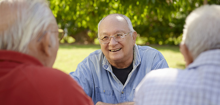 Three men sitting outside talking