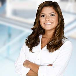A business professional with her arms folded in front of her smiling