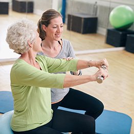 A rehabilitation team member assisting a resident with dumbbell exercises