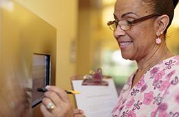 smiling nurse using wall mounted technology