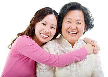 young girl hugging an elderly woman