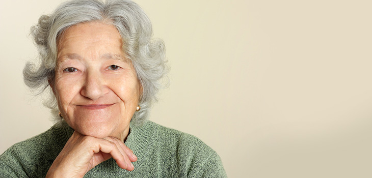smiling elderly woman with her chin on her hand
