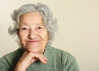 smiling elderly resident with her chin on her hand
