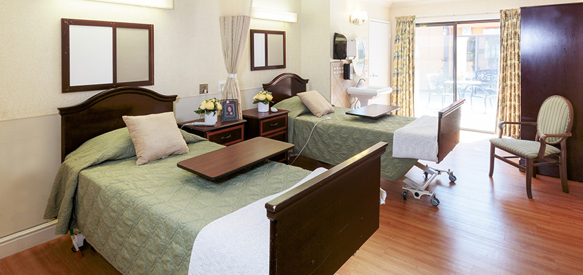classy wooden framed beds with a bed table and chair
