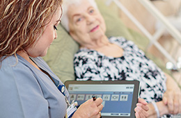 nurse using a tablet helping a patient laying down