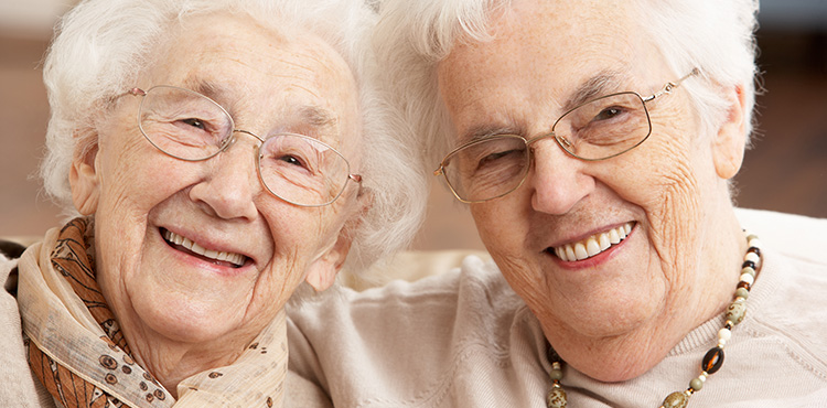 2 elderly female friends with big smiles