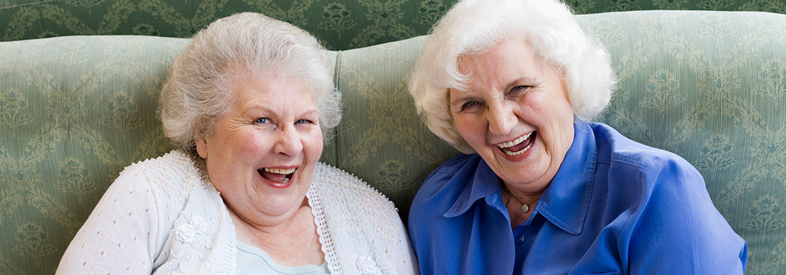 2 female friends laughing while seated on a couch