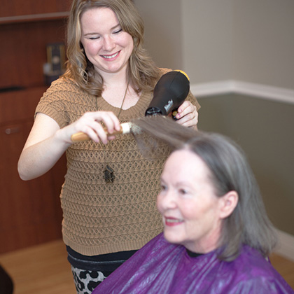 resident having her hair styled