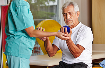 male resident lifting small hand weights with therapist