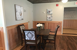 Resident dining area with flowers on the table and wood floors