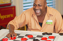 Laughing man playing checkers