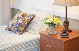 bed with nightstand and flowers