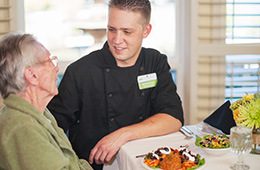 waiter serving food to resident