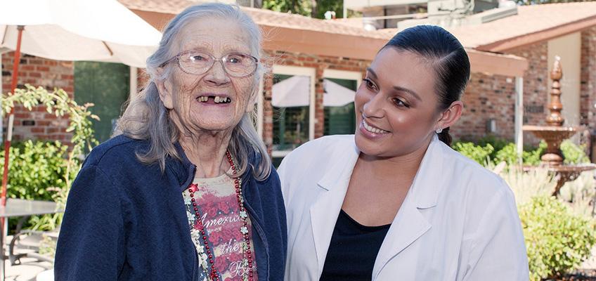 smiling elderly female resident with smiling nurse
