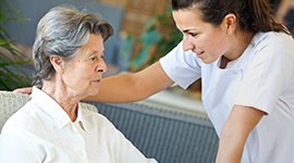 woman sitting with a nurse talking to her