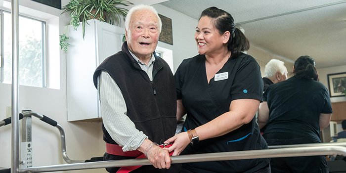 smiling therapist assisting a resident on the parallel walking therapy bars