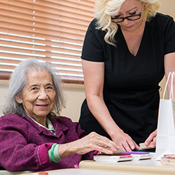 resident doing a craft project with a staff member