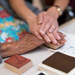 close up photo of activity director and a resident's hands doing an ink stamping craft project