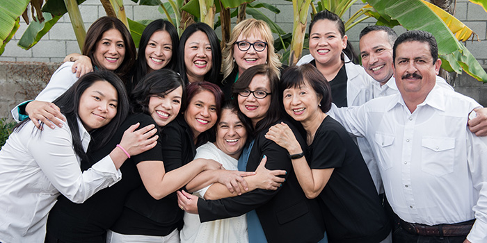 Staff photo where everyone is smiling and embracing
