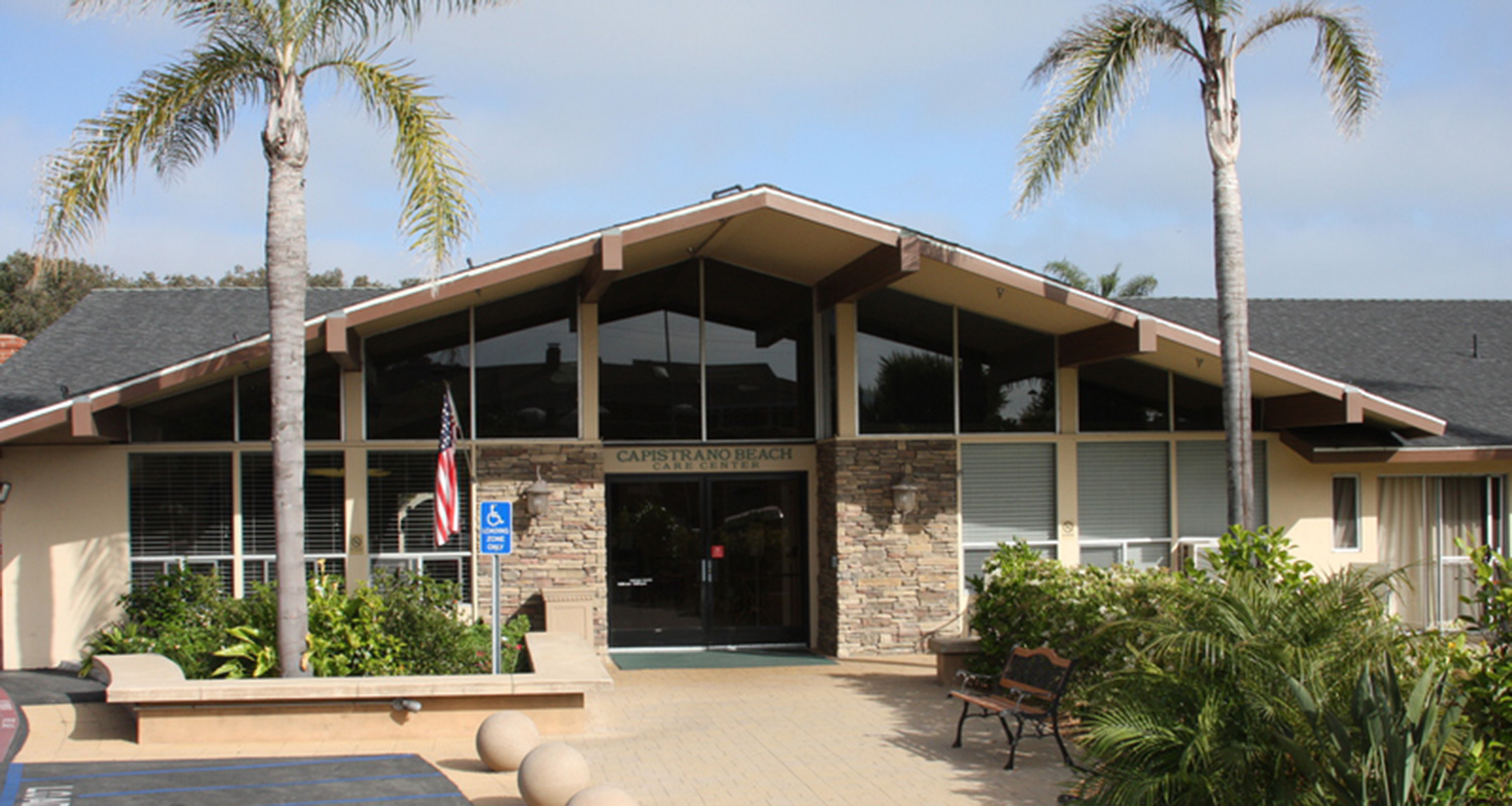 Capistrano Beach Care Center front entrance of building flanked by palm trees