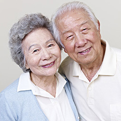 smiling couple with their heads tilted towards each other