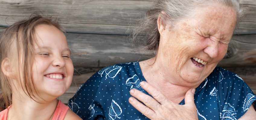 Elderly woman having a good laugh with young girl