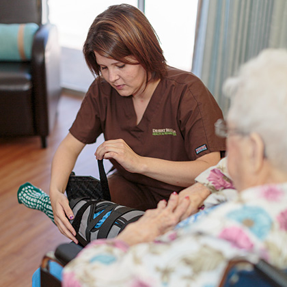 nurse wrapping knee brace for resident