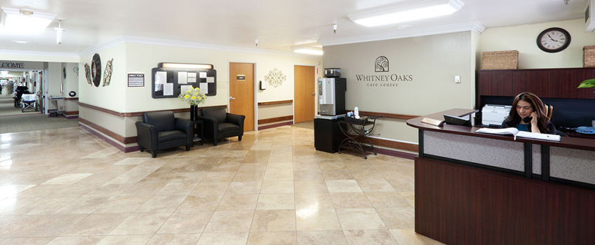 lobby of whitney oaks with large tiled floor and clean walls and desks